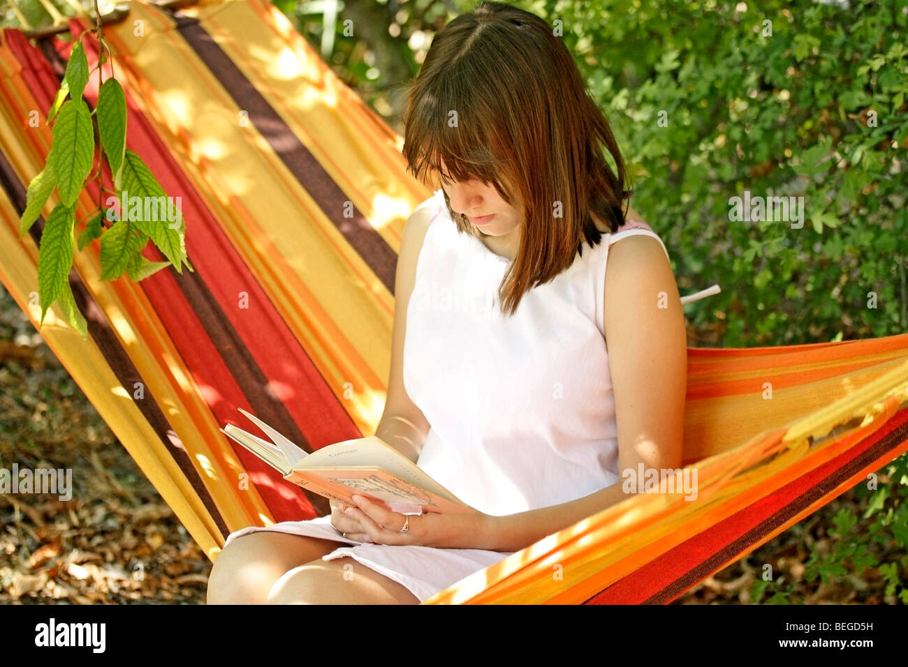 Reading in a hammock - Stock Image