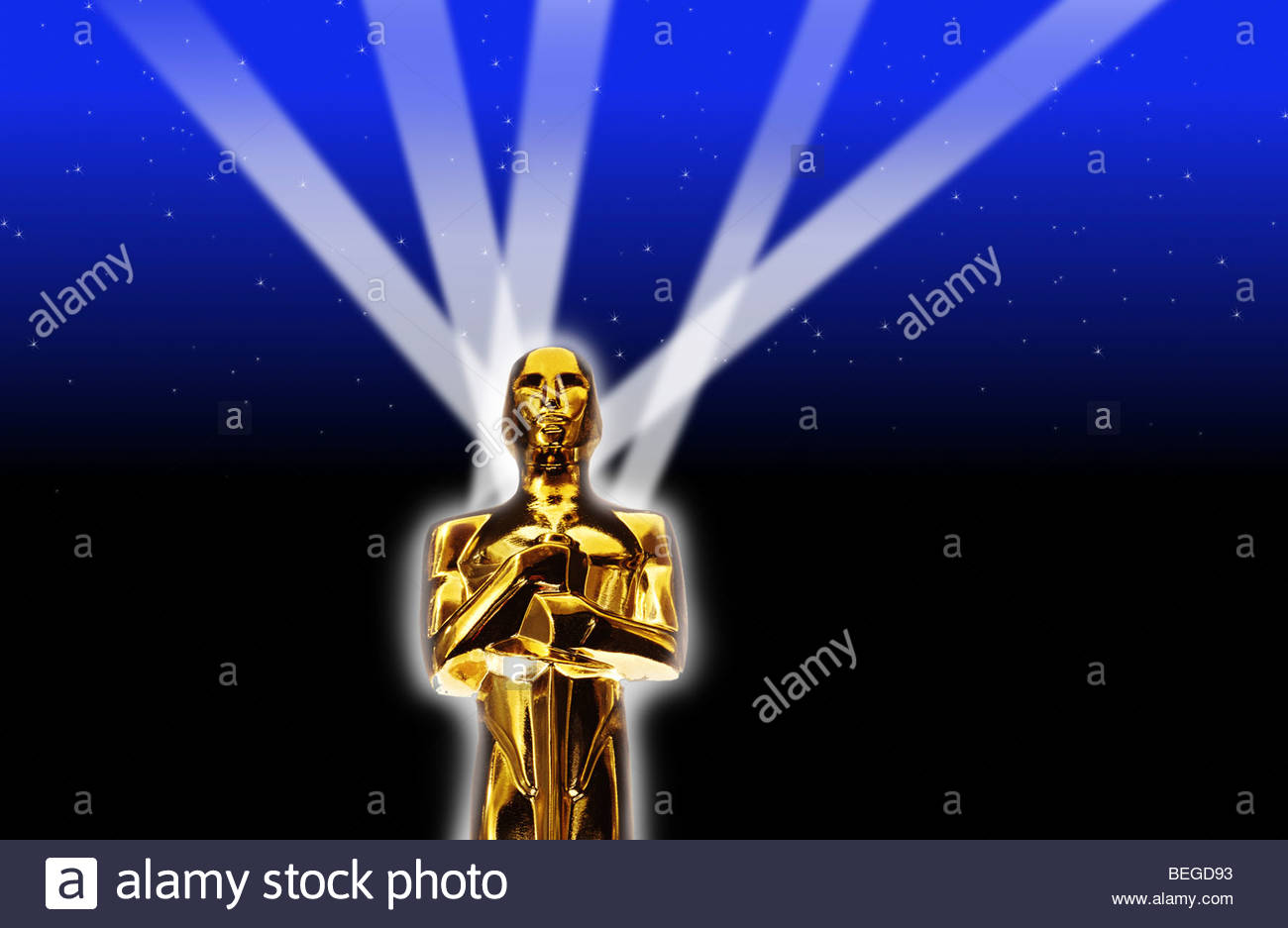 An Oscar statue with searching lights. - Stock Image