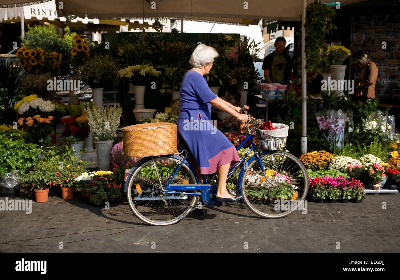 Woman buying flowers on bicycle, Campo dei Fiori, Rome, Italy - Stock Image