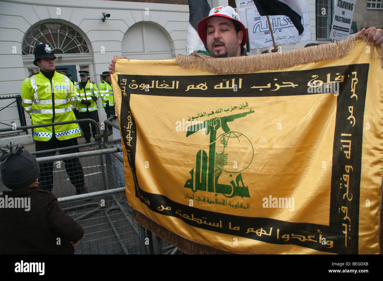 Police outside Egyptian Embassy and man with Hezbollah flag at protest calling for Gaza border to be reopened - Stock Image