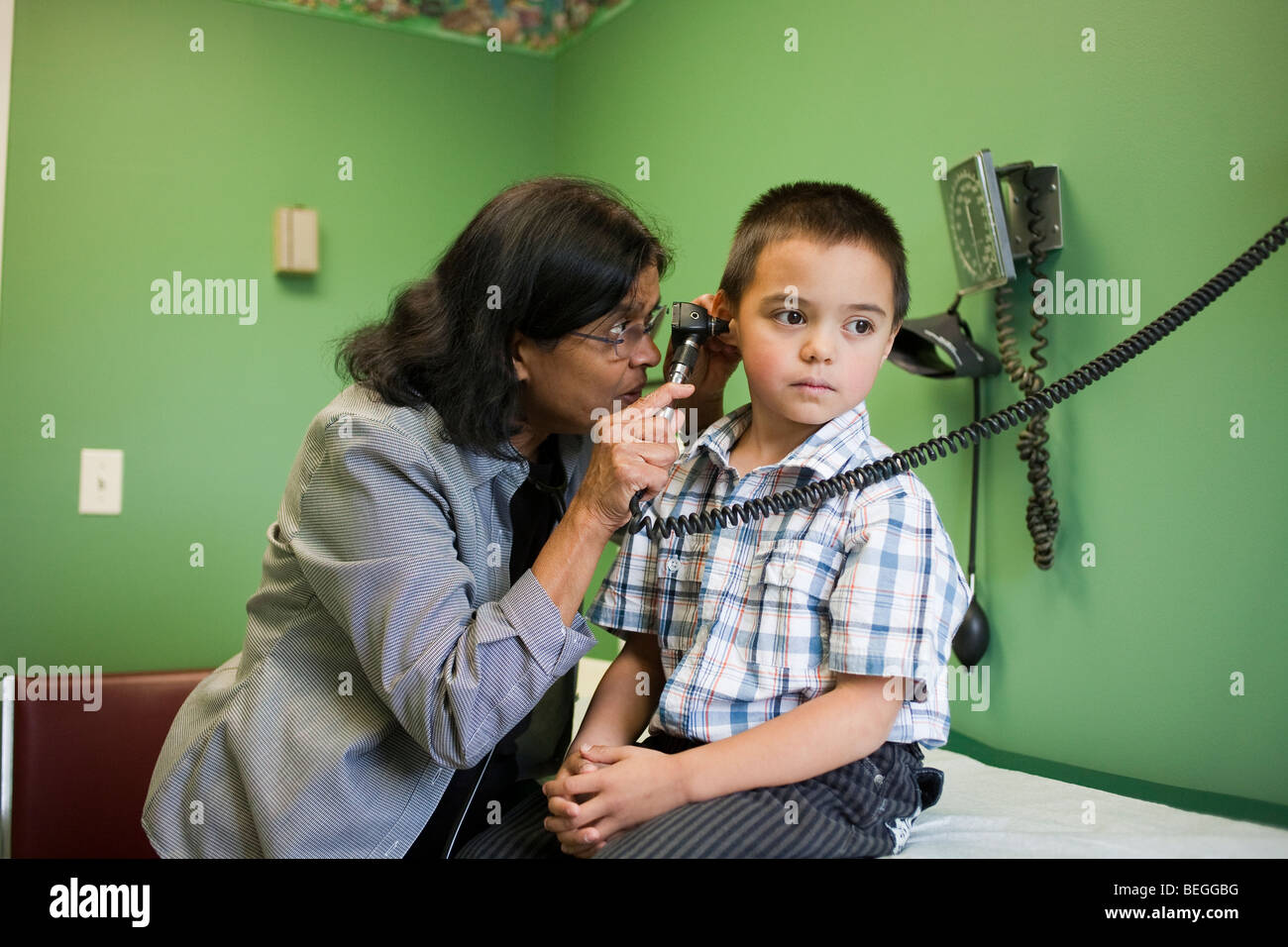 5 year old boy getting an examination at the doctors office - Stock Image