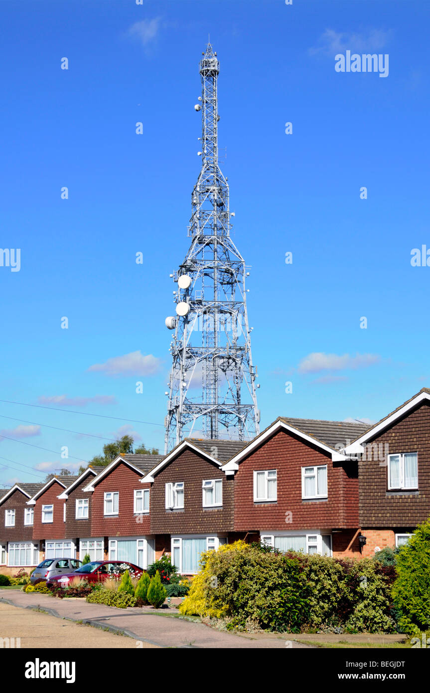 Telecommunications mast rising above row of houses - Stock Image
