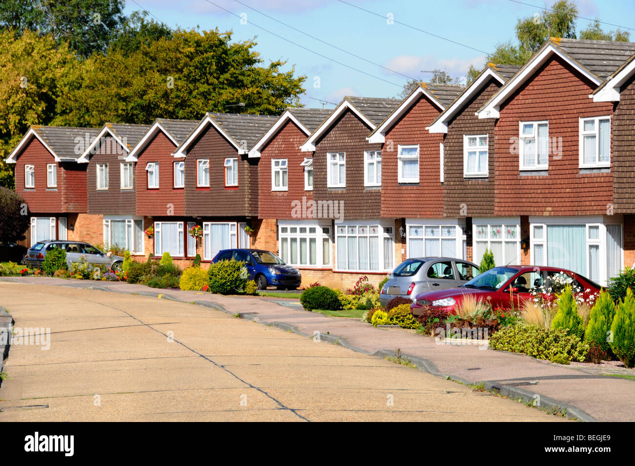 Row of homes in residential street of real estate housing property development identical detached houses individual Stock Photo
