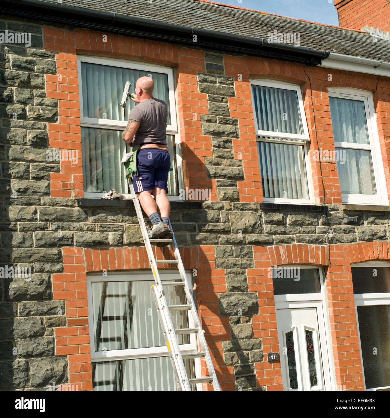 Self employed man sole trader standing on ladder cleaning windows of a terraced house, Aberystwyth Wales UK - Stock Image