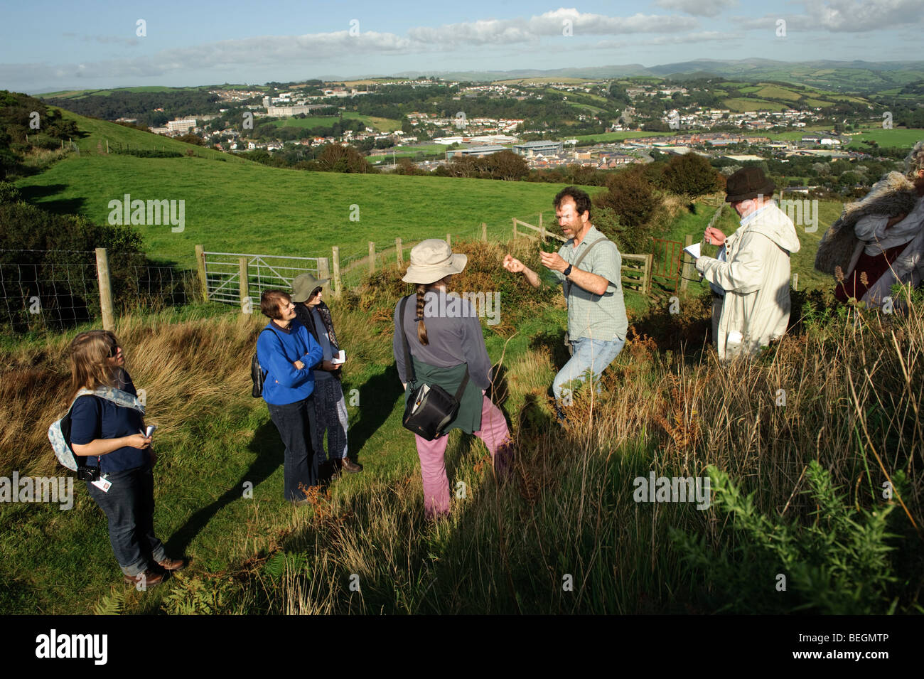 A botanist with the Countryside Council for Wales leading a bio-diversity nature walk up Pendinas Hill fort, Aberystwyth, - Stock Image