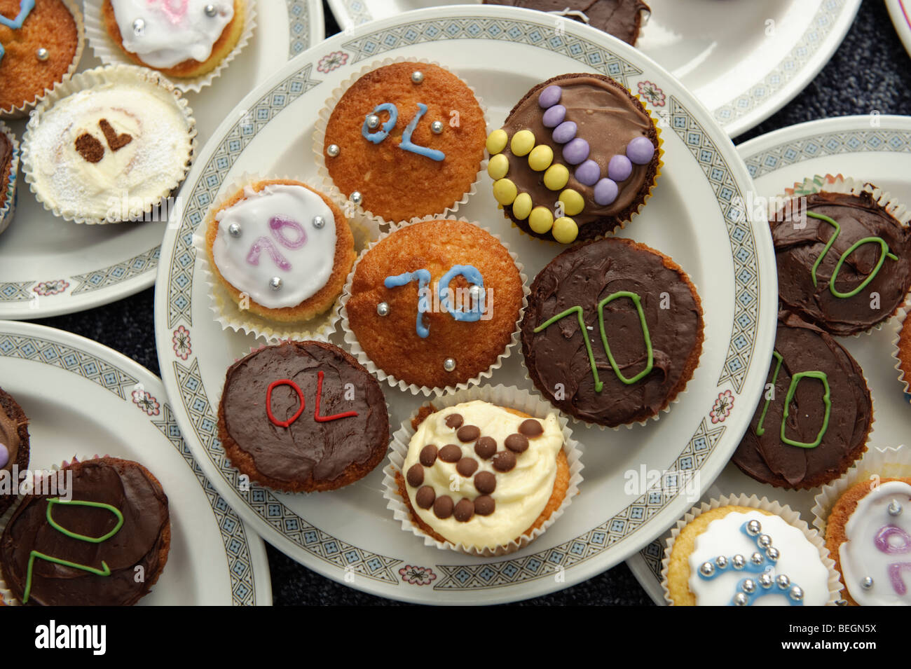 Plates of little iced cup cakes for a 70th birthday party UK - Stock Image
