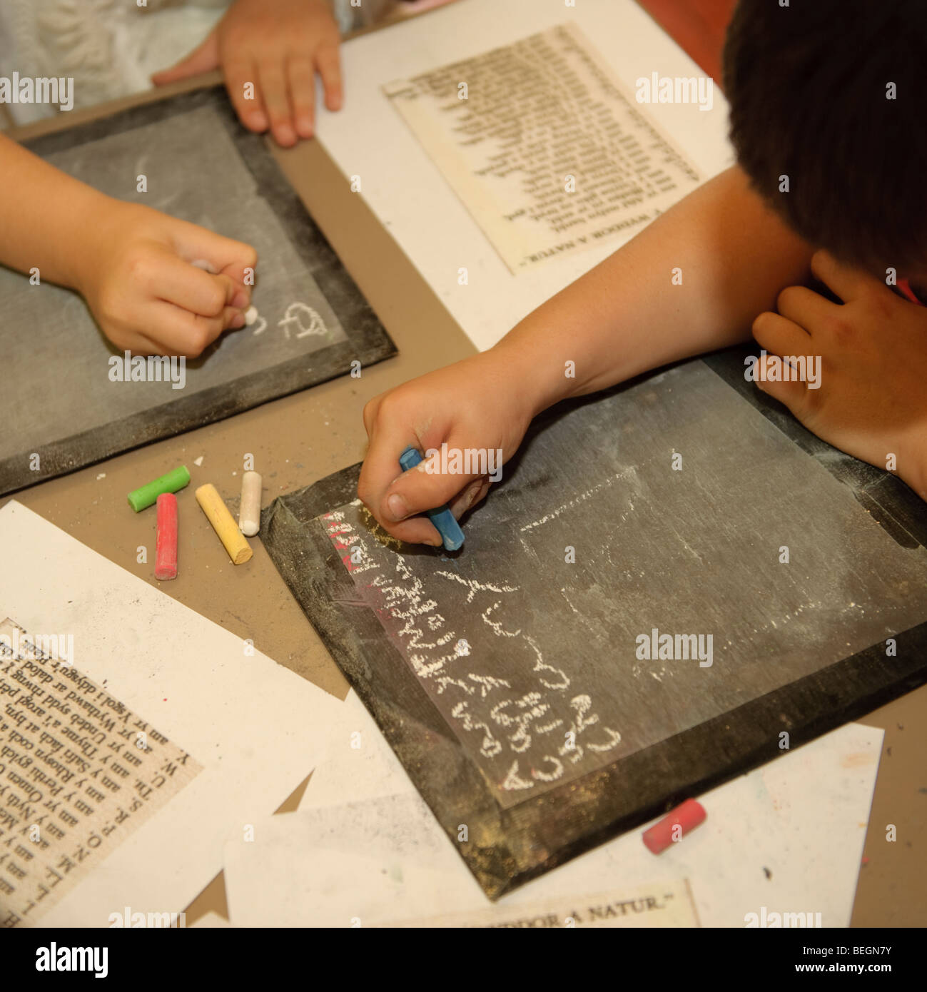 Children in a primary school class writing in chalk on old fashioned slate tablets during key stage two history - Stock Image