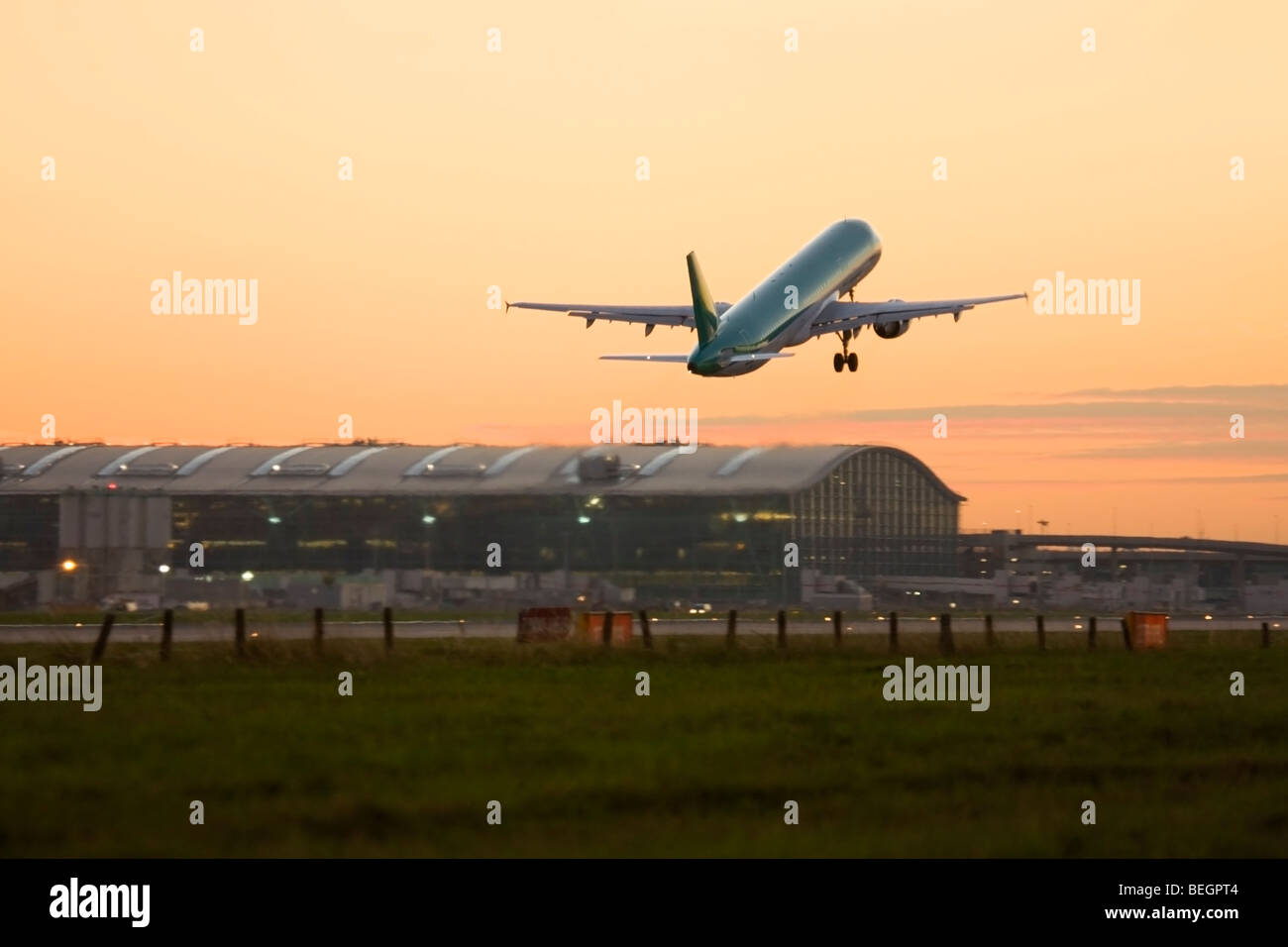 Commercial airplane taking off at London Heathrow Airport with Terminal 5 in the background, UK Stock Photo