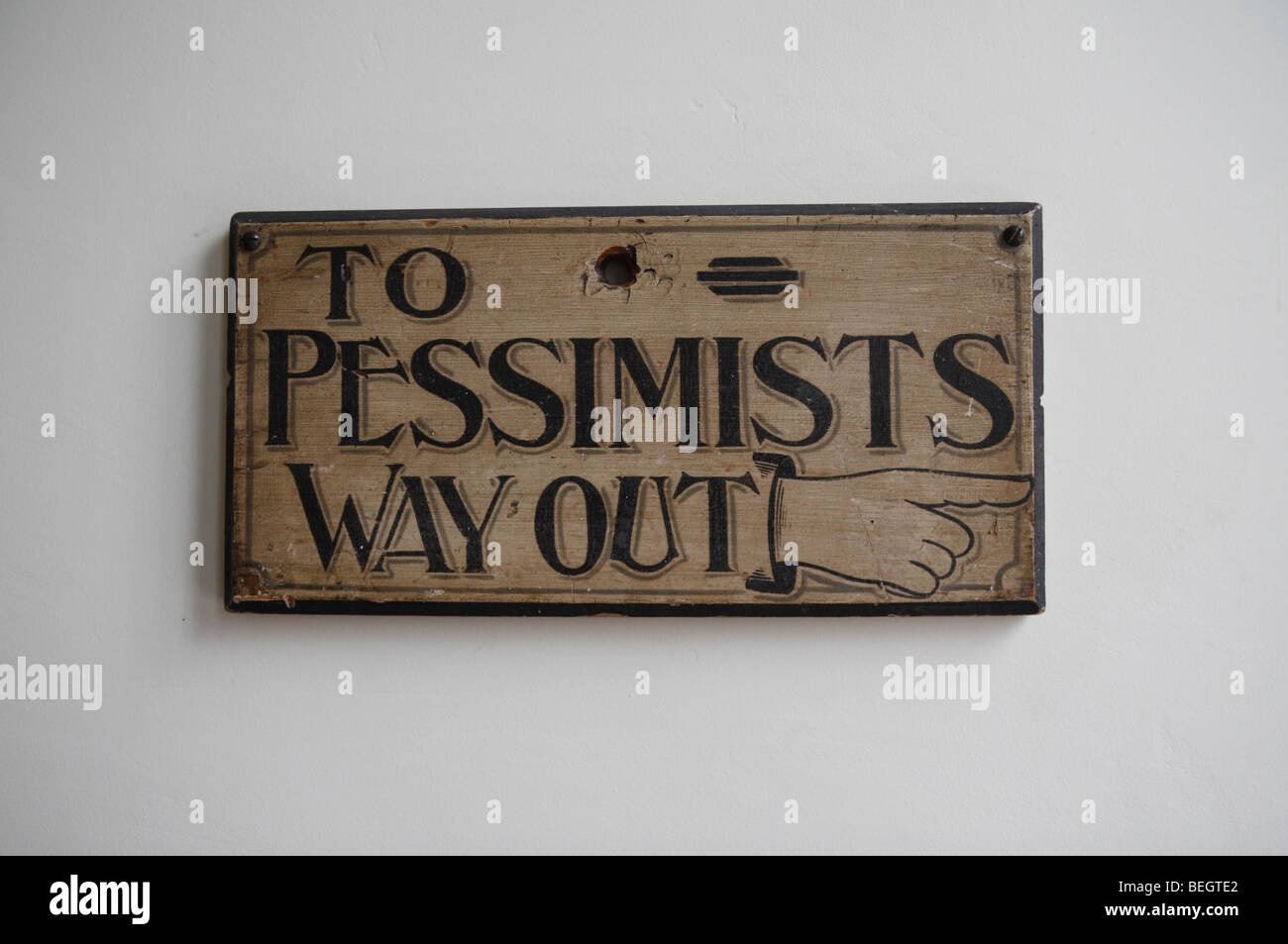 Amusing sign in the entrance hall of Talbot House, Poperinge, Belgium pointing all pessimists back out the door - Stock Image