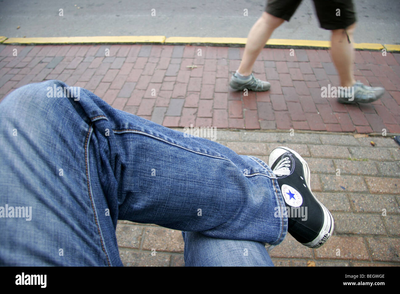 3e57dce17b0 Person in jeans and Converse shoes sitting crossed legged outside as a  second person walks past.