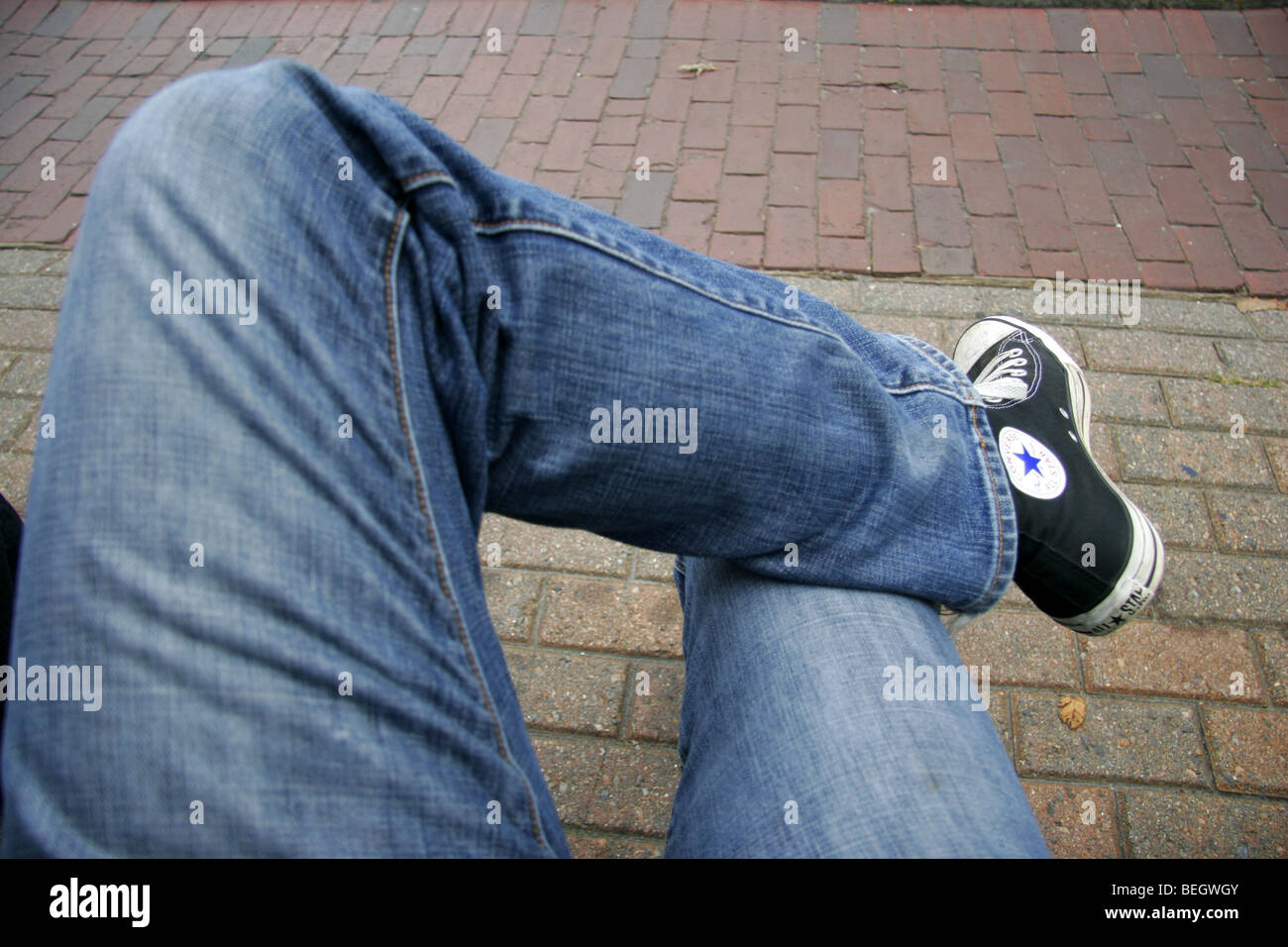 6f957e2eec2 Person wearing blue jeans and Converse shoes sitting cross legged outside.