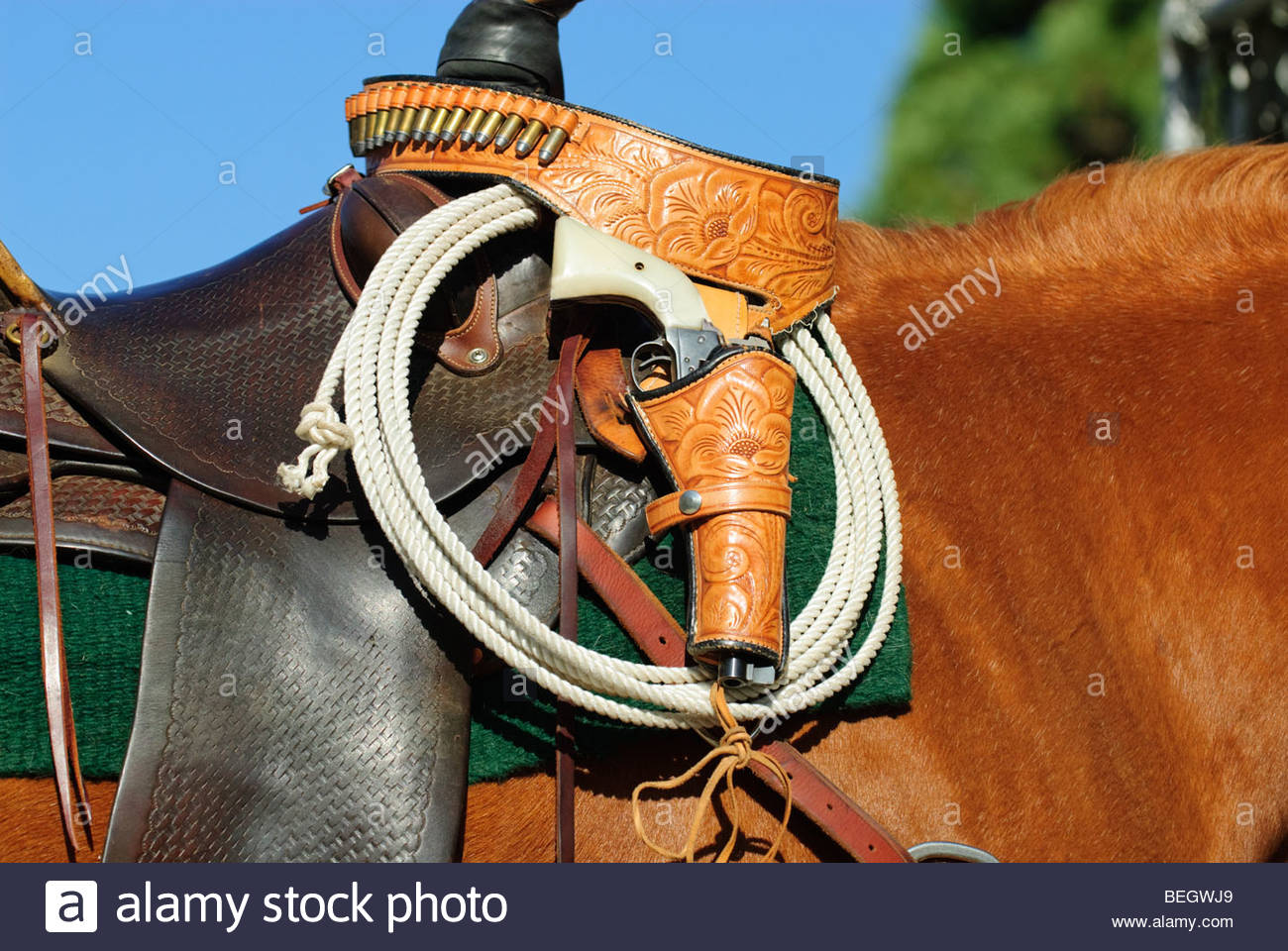 well worn saddle with lasso attached and gun holster slung over the saddle horn - Stock Image