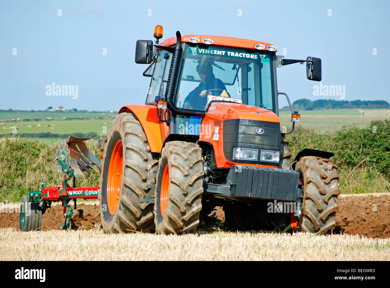 a tractor ploughing a field in late summer,cornwall,uk - Stock Image