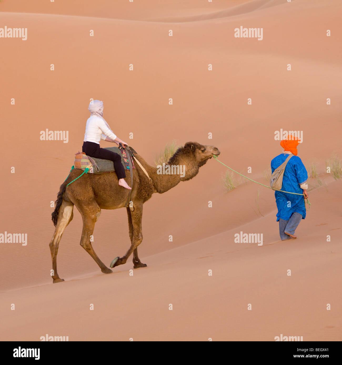 Tourist on a camel ride Merzouga Dunes Sahara Morocco Stock Photo
