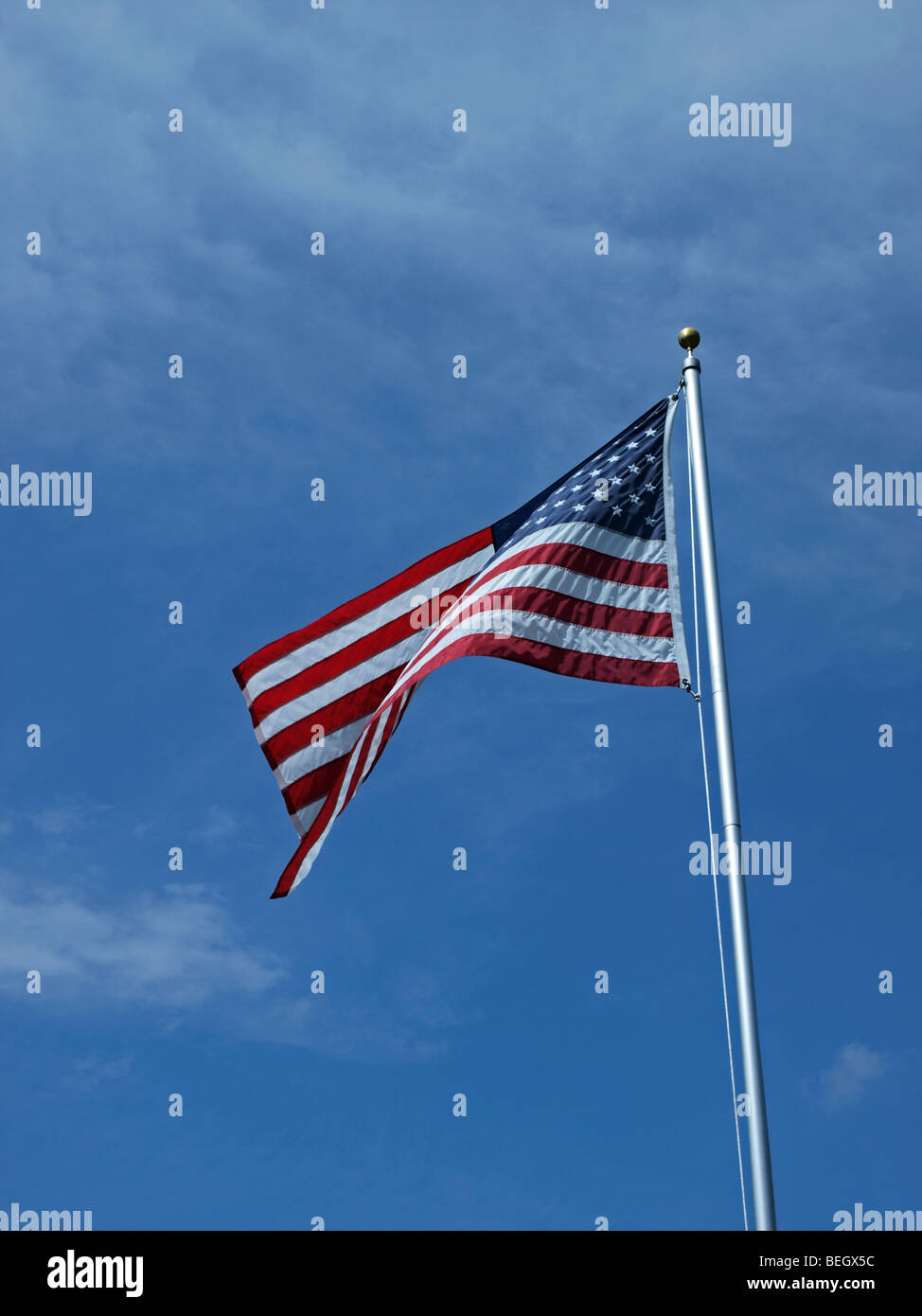 USA flag 'old glory' flowing on top of tall flagpole with blue sky behind - Stock Image