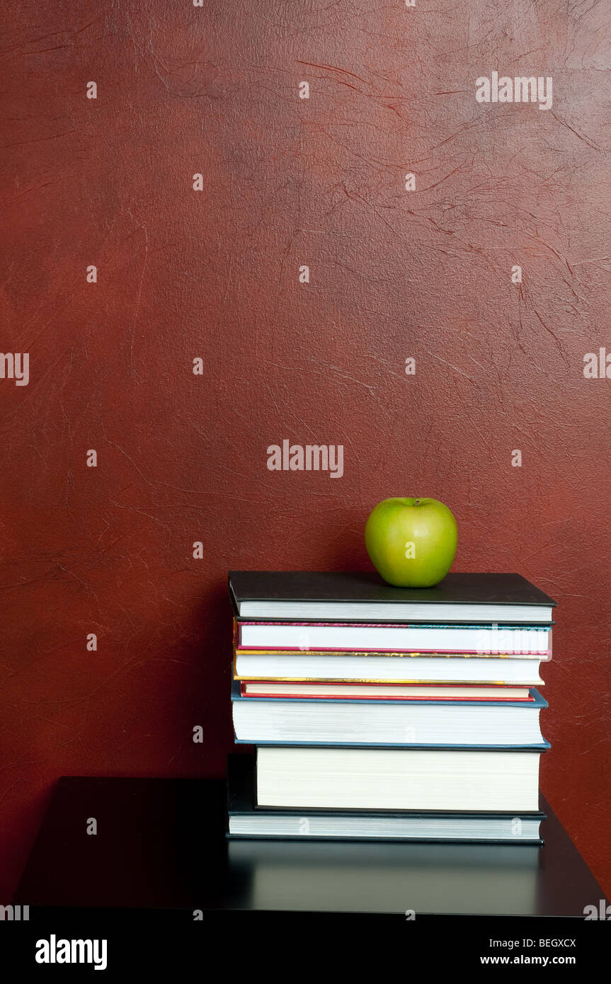 Vertical image of a stack of books with a green apple - Stock Image