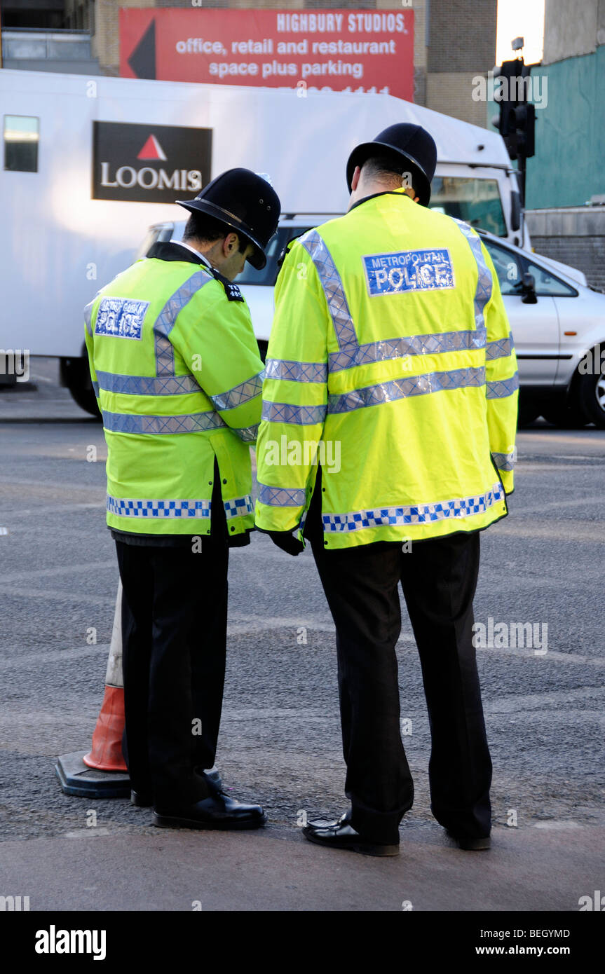 Two Metropolitan Police Officers in yellow reflective jackets standing in Holloway Road London England UK - Stock Image