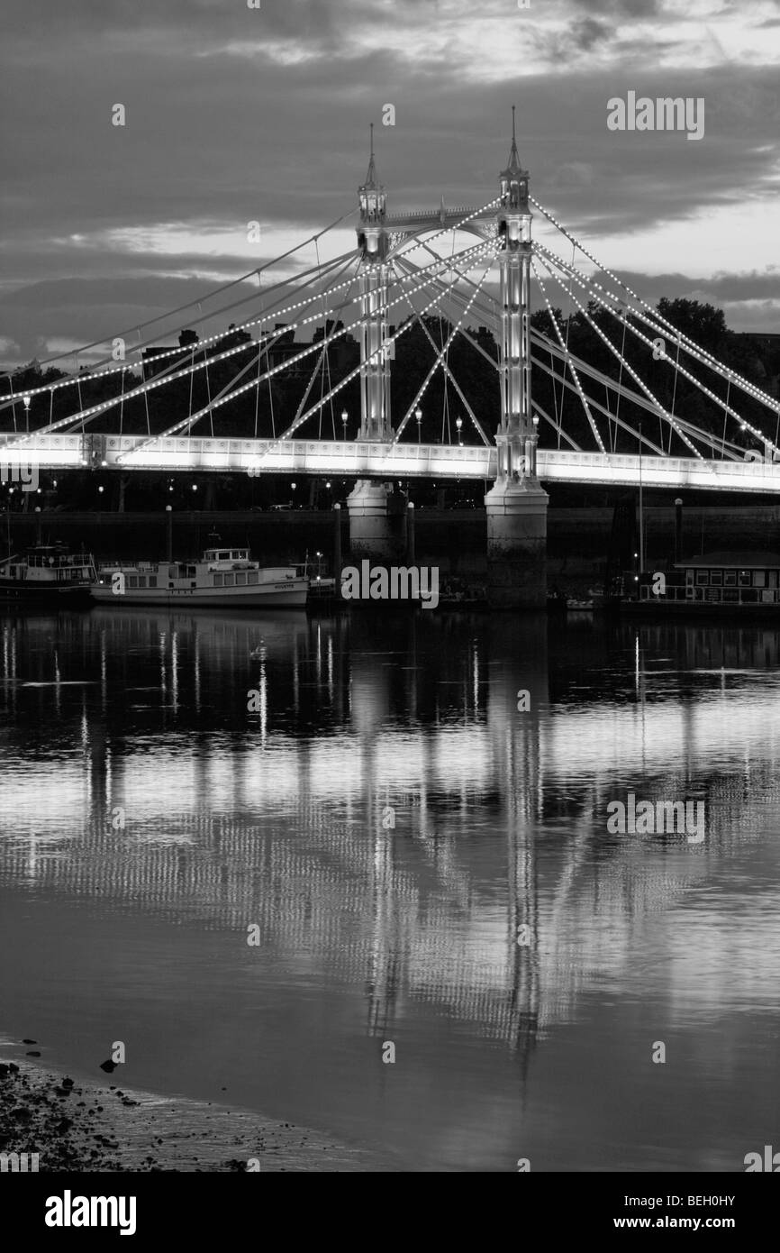 Dusk falls over the Albert Bridge and the River Thames in London England, during Summer 2009. - Stock Image