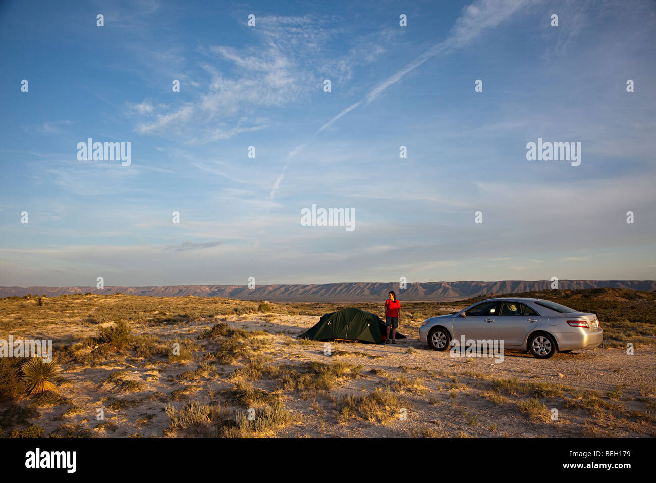Woman with tent and car camping in desert on BLM land New Mexico USA - Stock Image