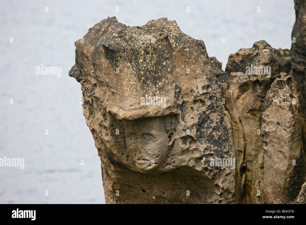 """A carving of """"the Priests head"""" near the Devils Churn at the Pans Rocks on Antrim coast. Northern Ireland. Stock Photo"""