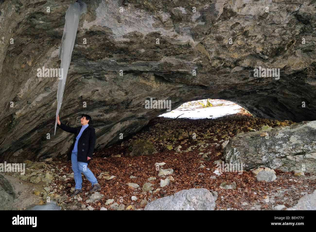 Woman looking at big icicle in a cave (Lengenfelsdurchgangshöhle), Baden-Württemberg, Germany - Stock Image