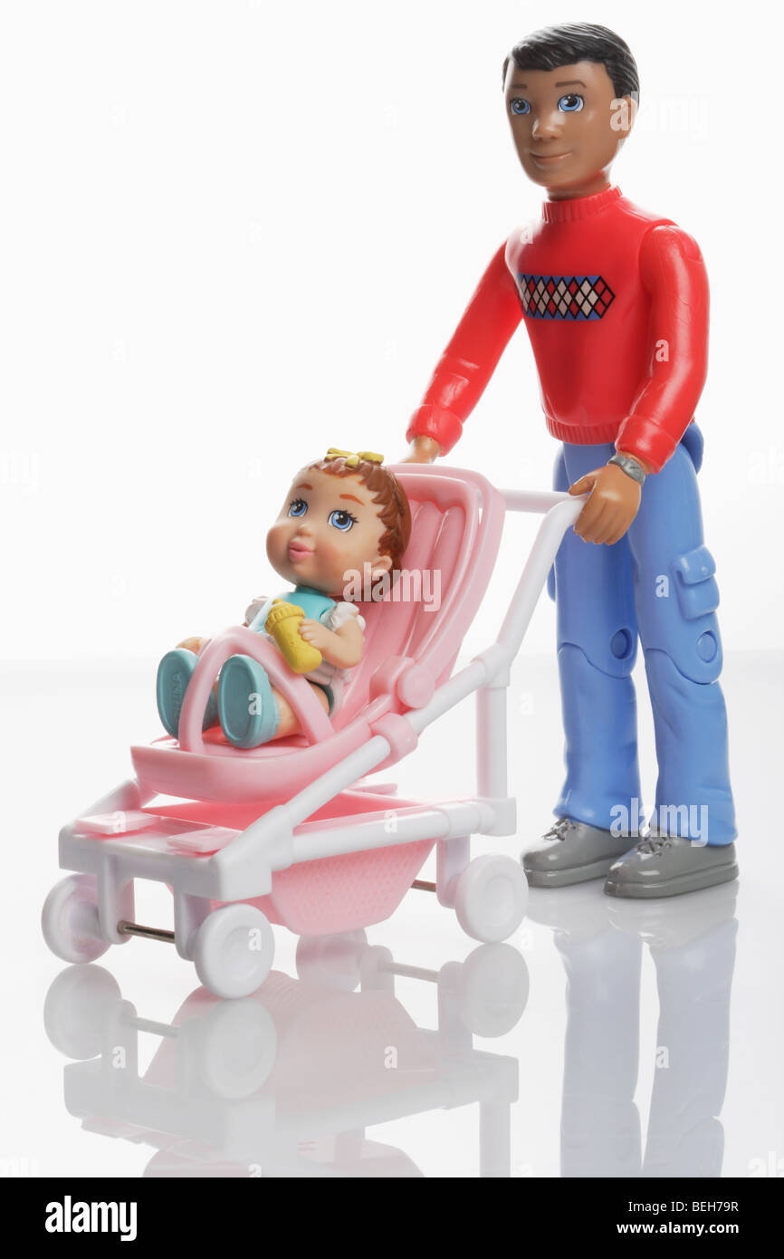 Father doll with baby girl doll in a miniature pushchair buggy Stock Photo