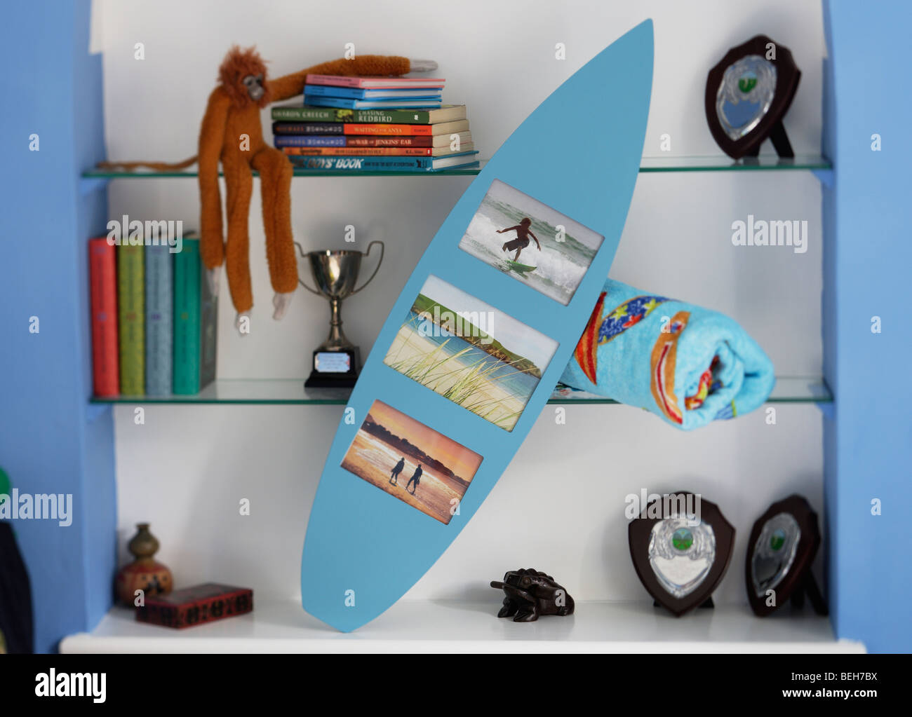 surfboard shaped photo frame in boys bedroom - Stock Image