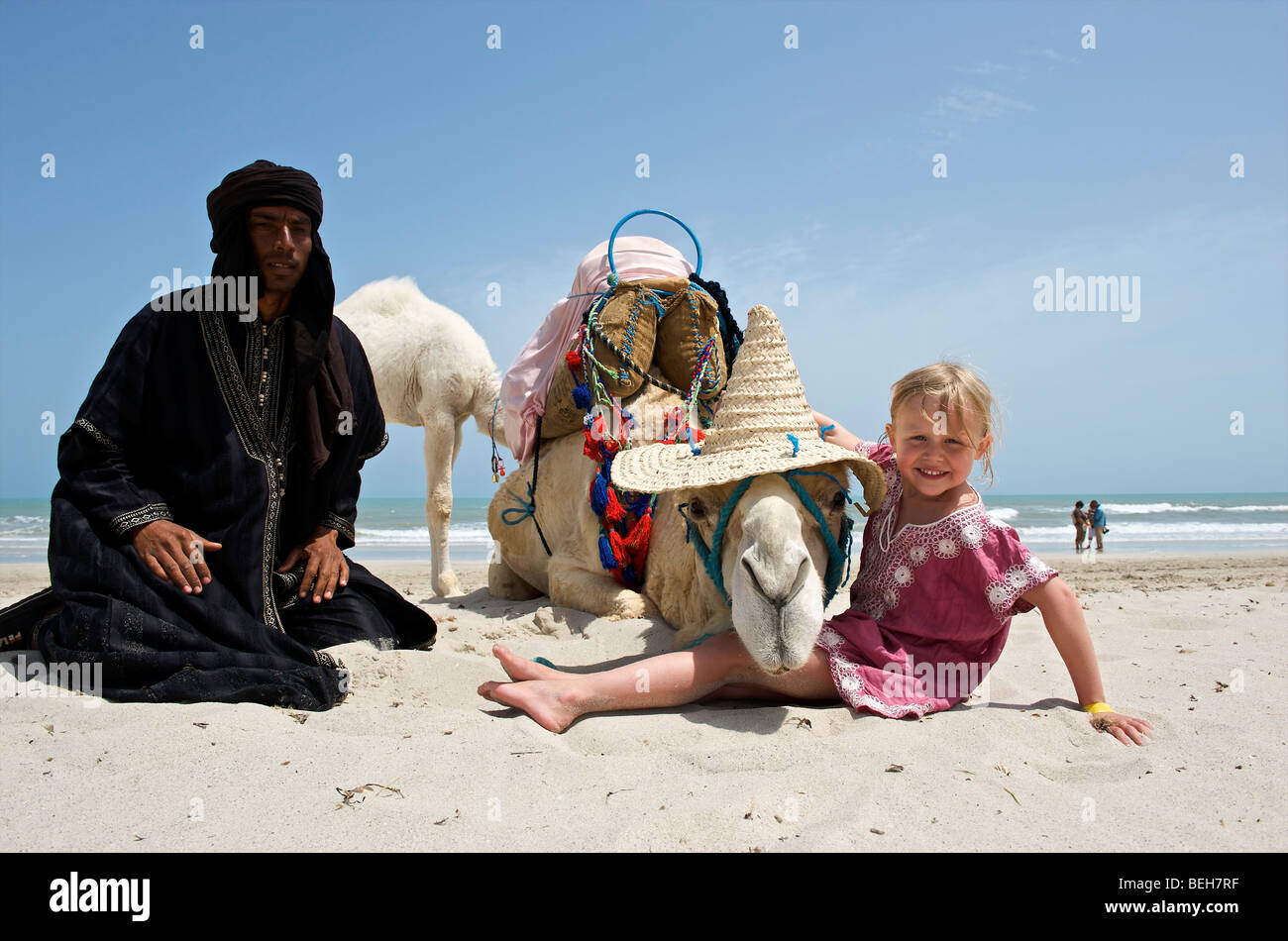 Tunesia, Djerba, Midoun, girl posing for photo together with a camel - Stock Image