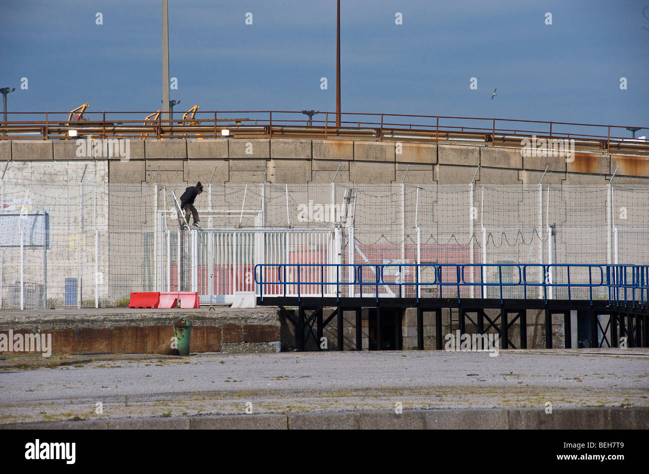 Calais, a refugee hoping to reach the UK by climbing onto a ship - Stock Image