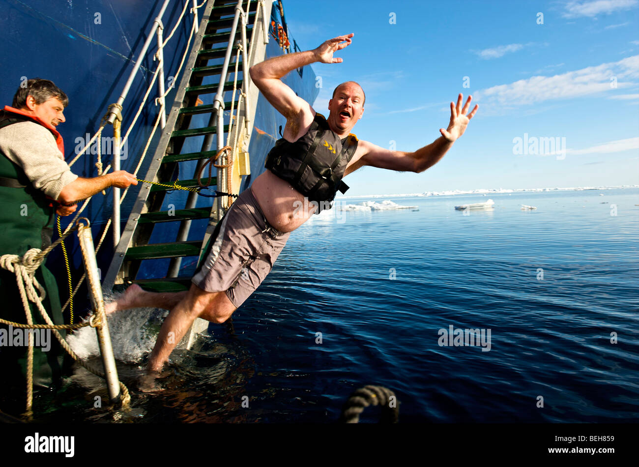 Passengers of the Akademik Shokalskiy take an arctic plunge - Stock Image