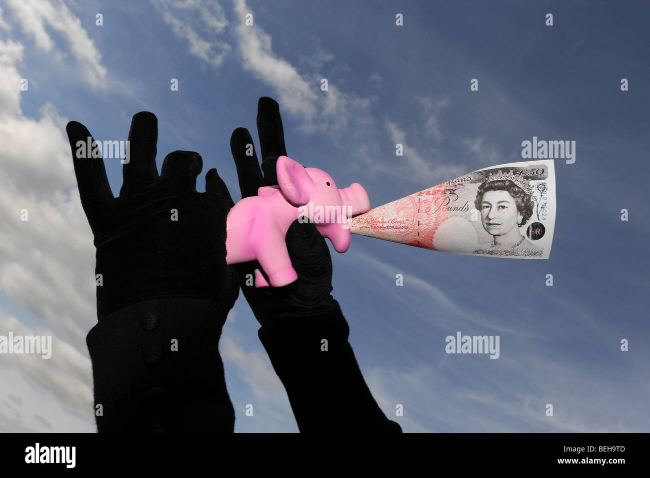 Financial squeeze on savings in piggy bank with low interest rates - Stock Image