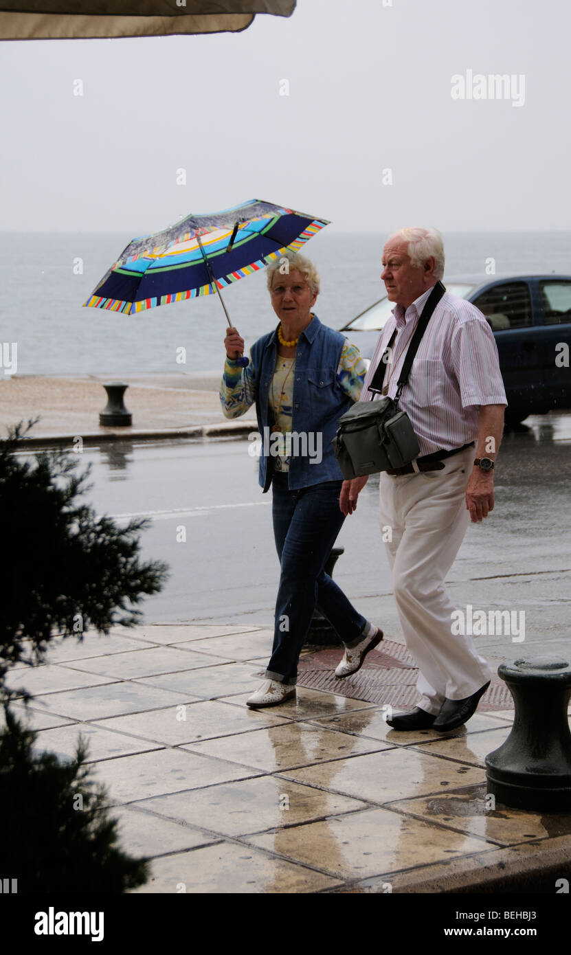 People on holiday  walking in the rain holding an umbrella - Stock Image