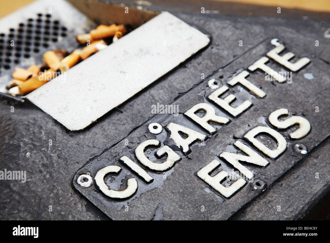 cigarette ends in ash tray - Stock Image