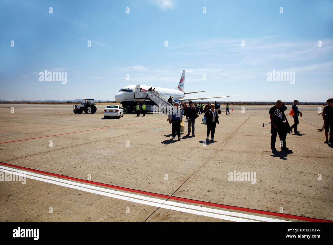 people walking off airplane, Windhoek Airport - Stock Image