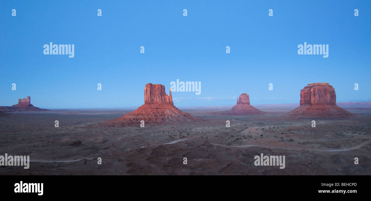 Monument Valley during the sunrise with crisp blue sky and red stones. - Stock Image