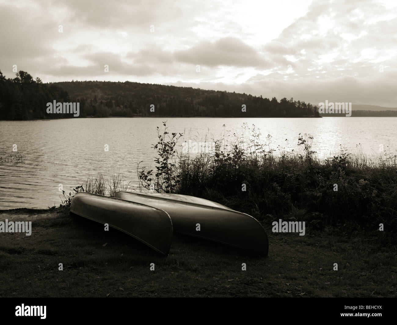Two canoe on a shore of The Lake of Two Rivers at dawn tranquil fall scenery. Algonquin Provincial Park, Ontario, Stock Photo