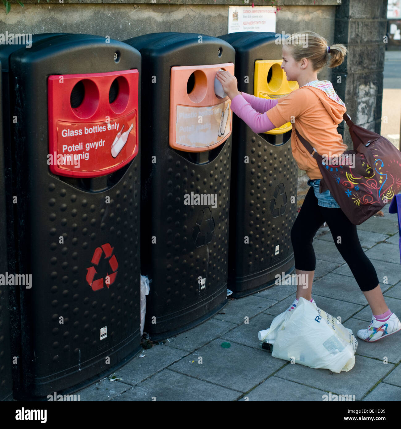 10 year old girl recycling plastic and glass bottles at a local authority operated mini bottle bank, Wales UK - Stock Image
