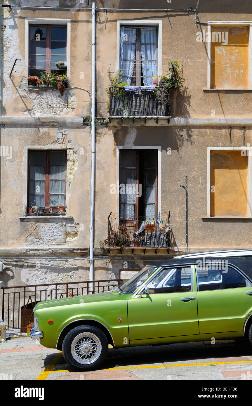 Old car and apartment building at the city center. Cagliari, Sardinia, Italy. - Stock Image