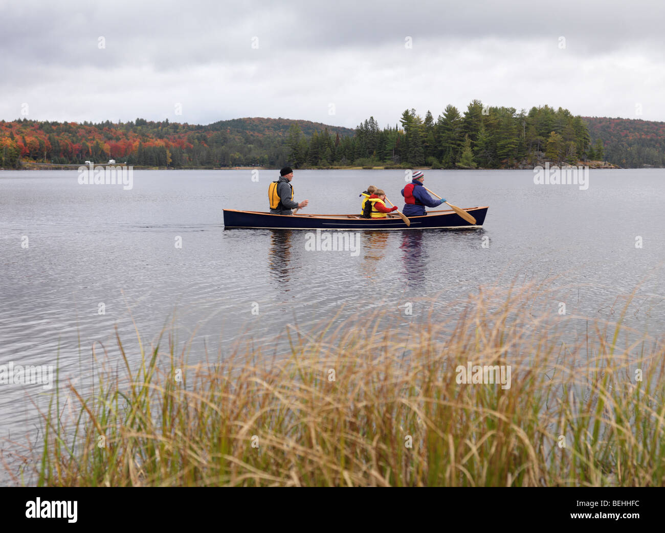 Family with children in a canoe on The Lake of Two Rivers in fall. Algonquin Provincial Park, Ontario, Canada. - Stock Image