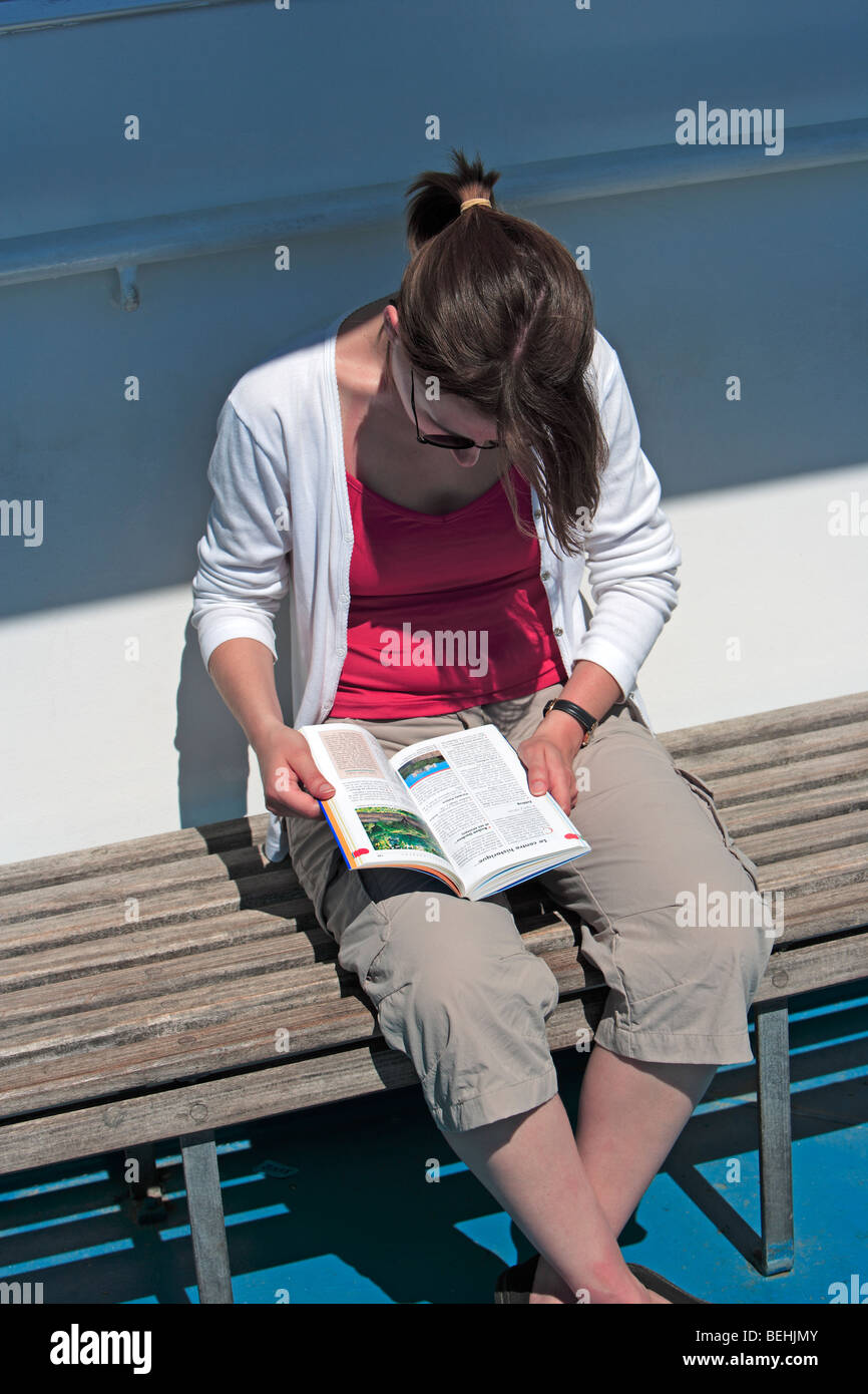 Tourist on ferry reading travel guide - Stock Image