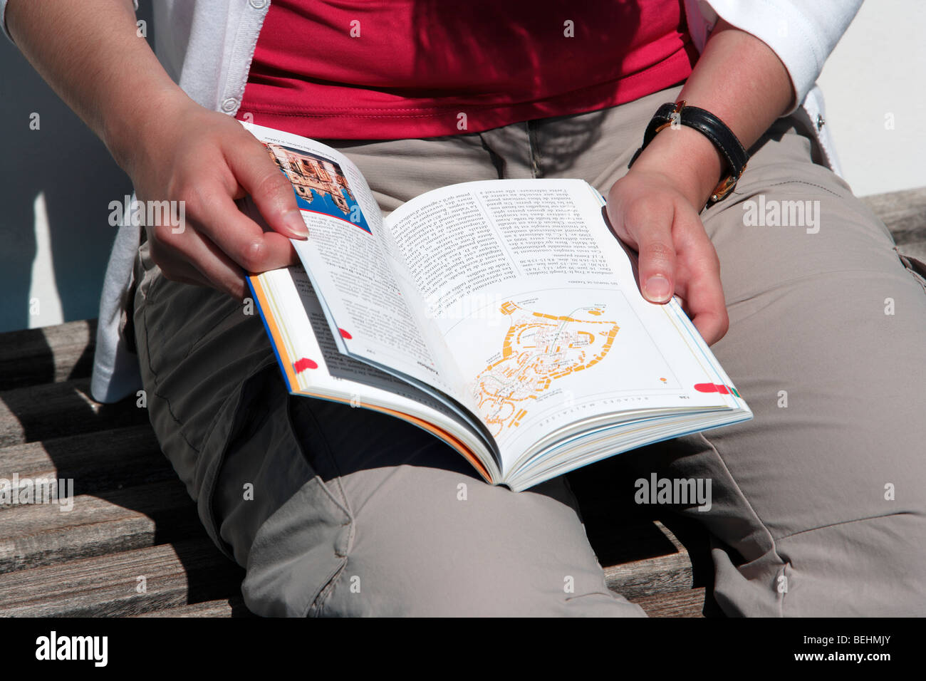 Tourist reading guide book - Stock Image