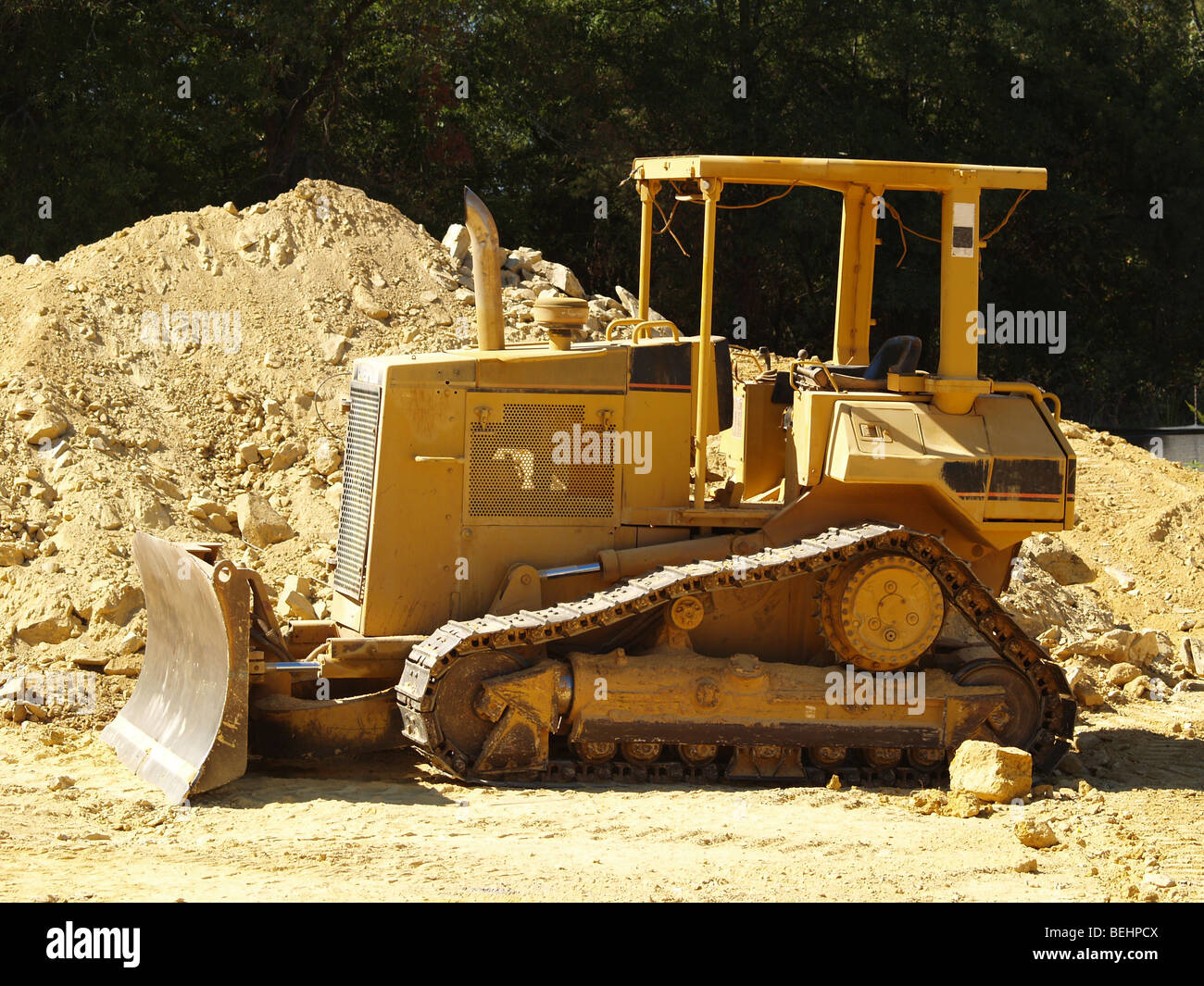 A heavy equipment earth moving bulldozer on a dusty commercial construction site. - Stock Image