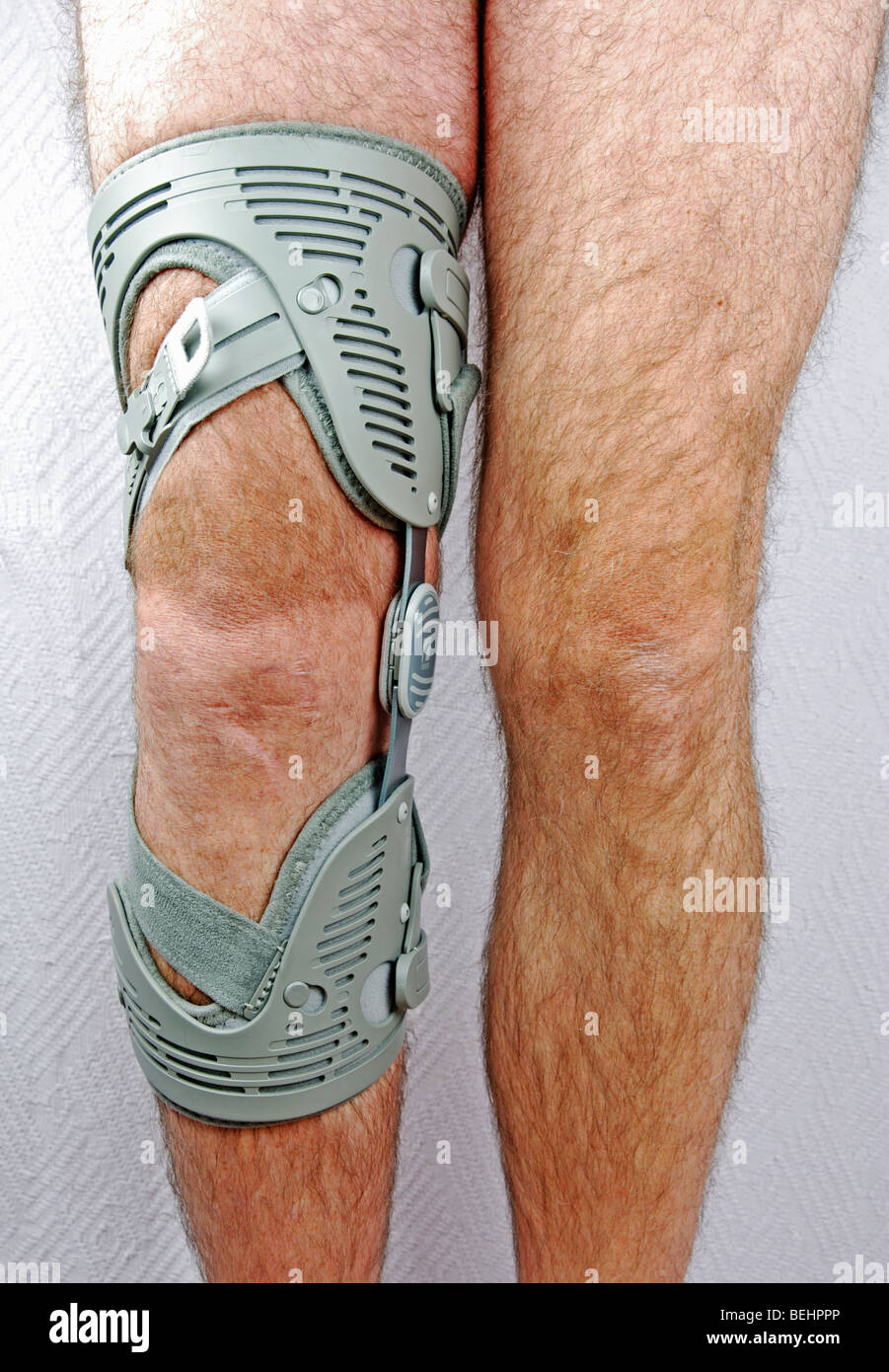 a man wearing a knee brace/support on an injured knee - Stock Image