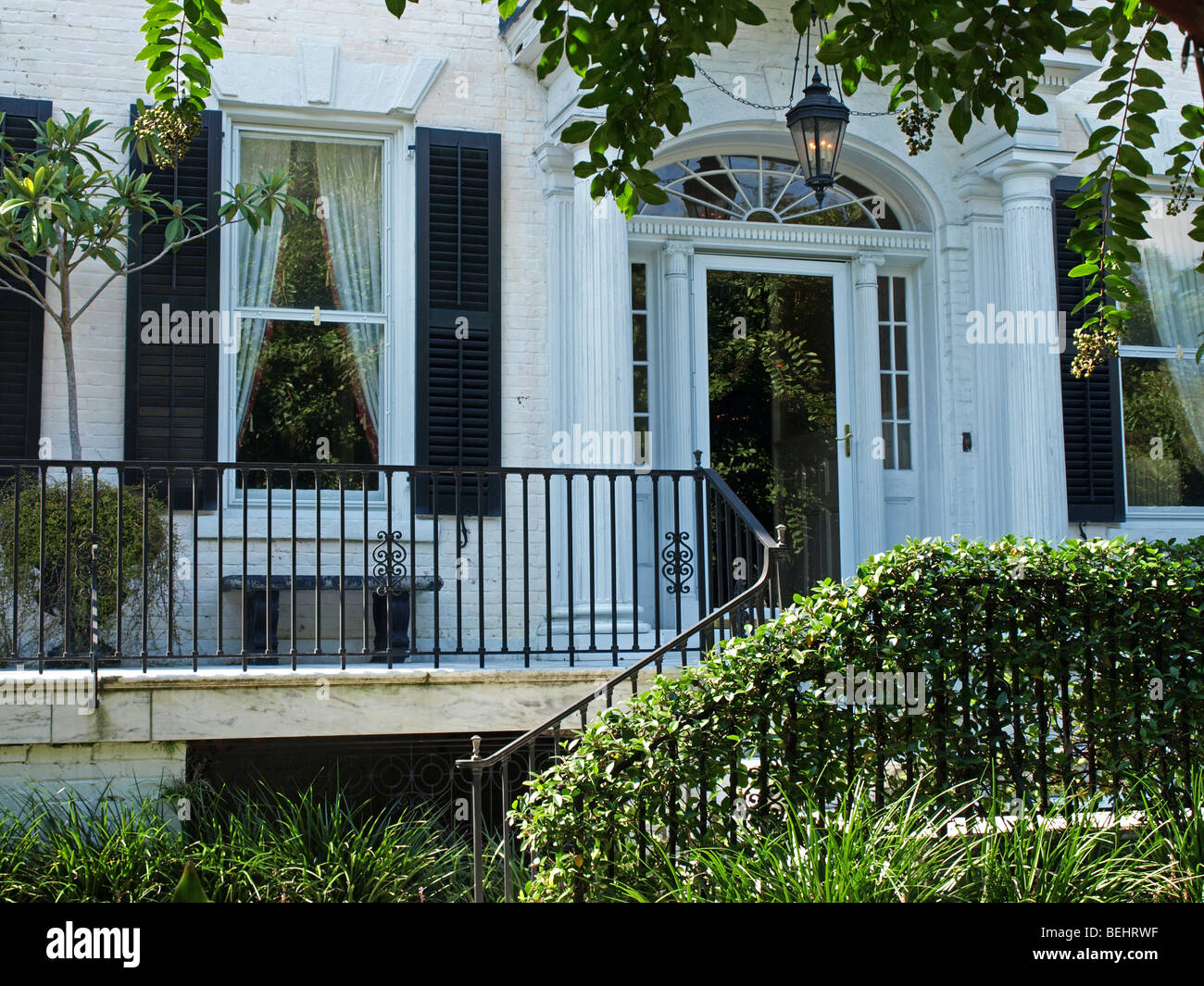 front entrance to historic house with columns windows and iron rail with bushes - Stock Image