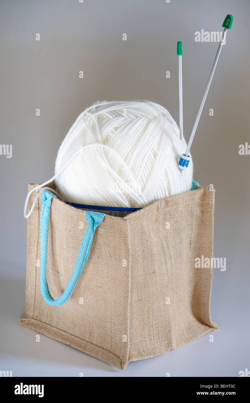Large ball of white 'Aran ply 'wool in a small brown hessian bag with a pair of knitting needles - Stock Image
