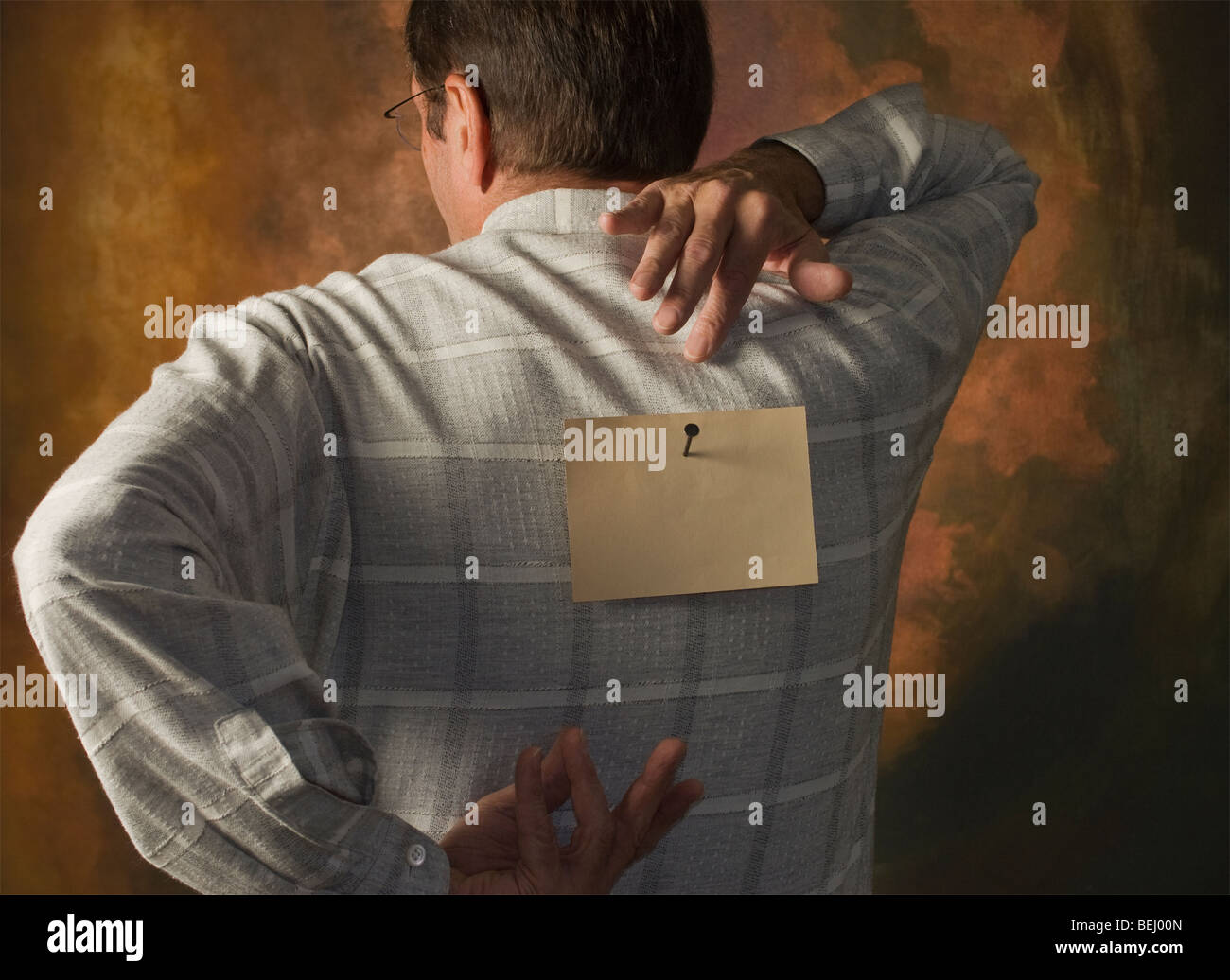 man reaching for note nailed to his back - Stock Image