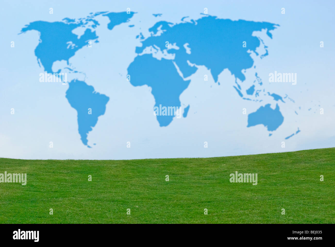 Outline of world map in blue sky above green grass - Stock Image