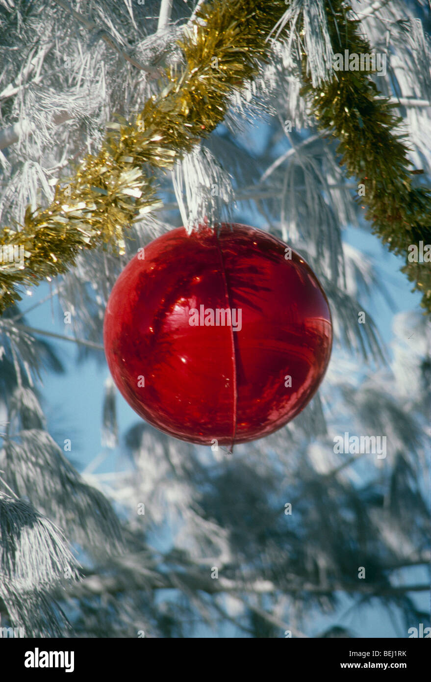 red glass christmas tree ornament with tinsel on a white flocked outdoor tree on a sunny winter day in the snow midwest usa