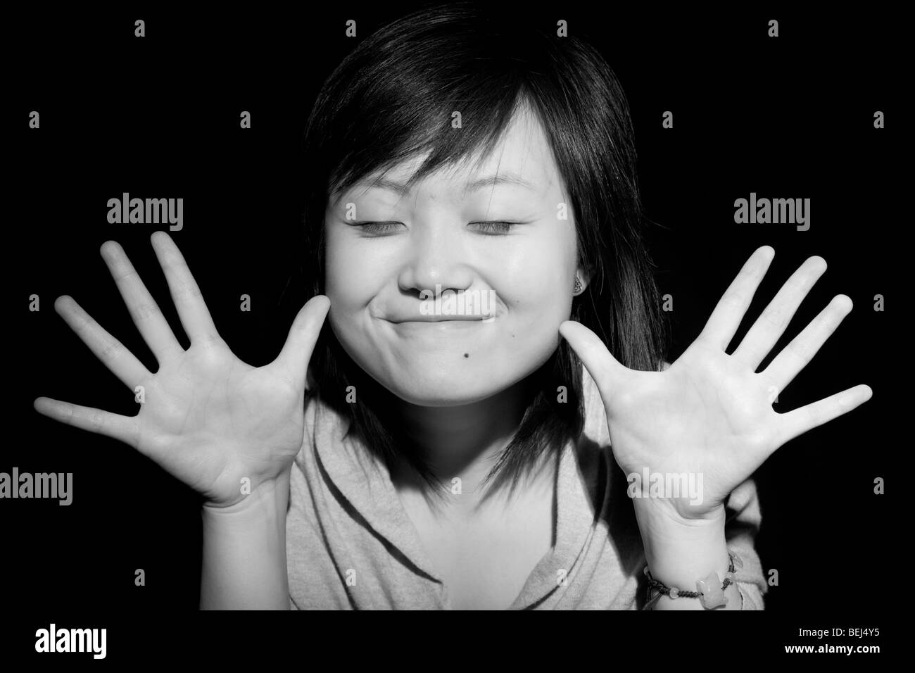Young Asian woman with a happy open handed gesture. - Stock Image