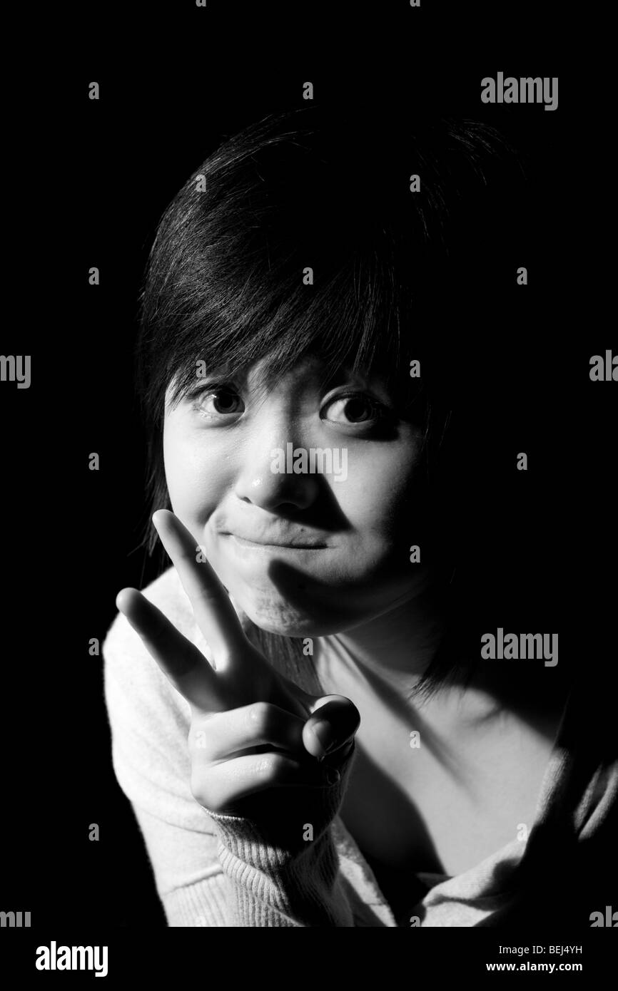 Young Asian woman making a cutting symbol with her hands. - Stock Image